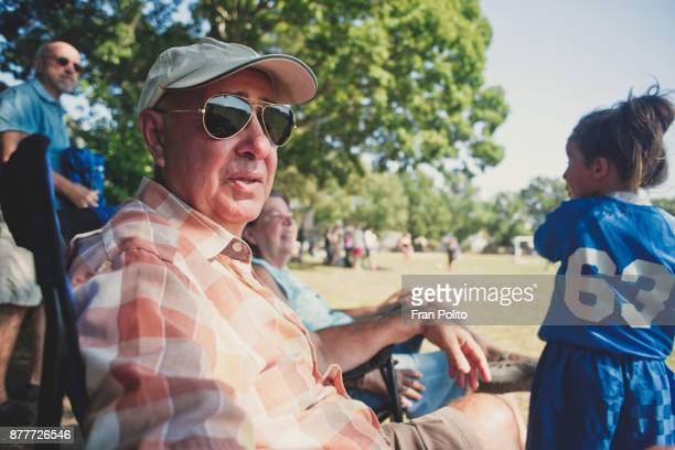 senior couple watching granddaughters soccer game. - sports event stock pictures, royalty-free photos & images