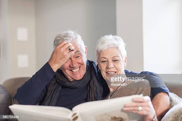 Senior couple watching photo album together