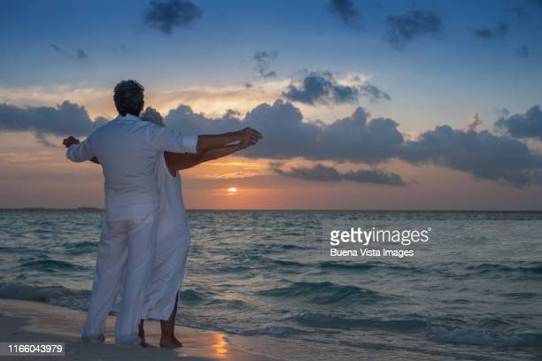 senior couple watching sunset - male maldives stock pictures, royalty-free photos & images