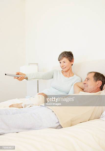 A senior couple watching television in bed together