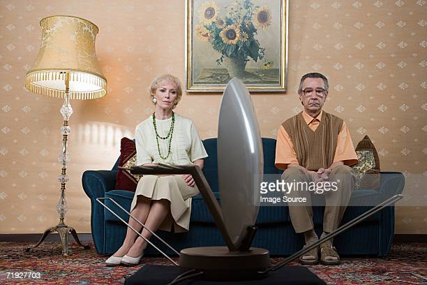 senior couple watching television - sulking stock photos and pictures