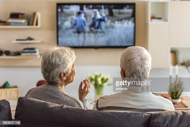 senior couple watching television show - television show stock-fotos und bilder