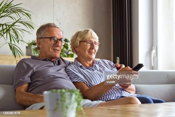 älteres paar, das zu hause fernsieht - izusek stock-fotos und bilder
