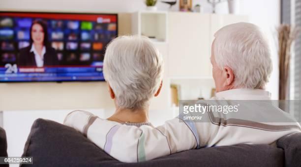 年配のカップルテレビを見る