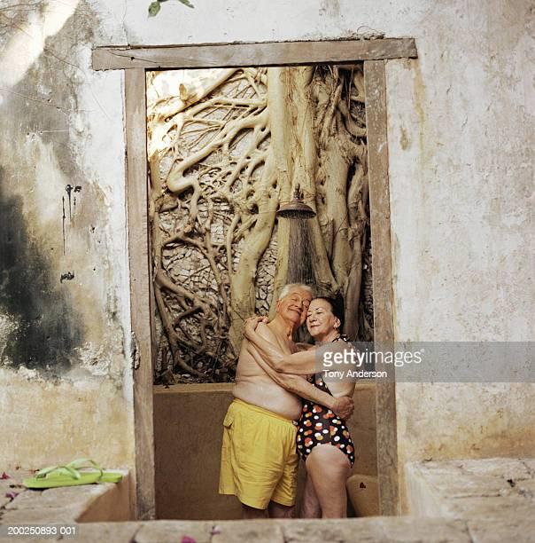 senior couple wearing bathing suits, embracing in doorway - frau unter dusche stock-fotos und bilder