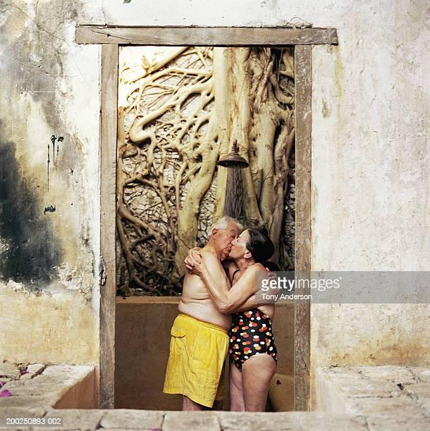 senior couple wearing bathing suits, kissing under shower head - frau unter dusche stock-fotos und bilder