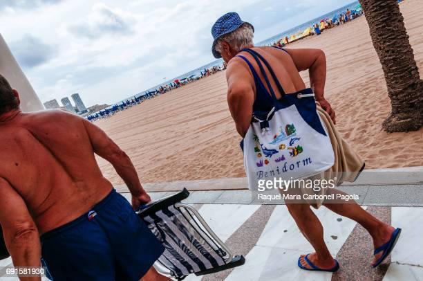 Senior couple wearing beachwear walking on beach promenade
