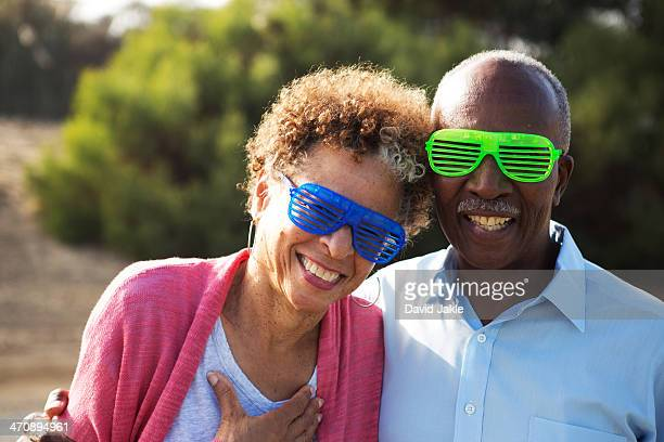 Senior couple wearing blue and green plastic glasses