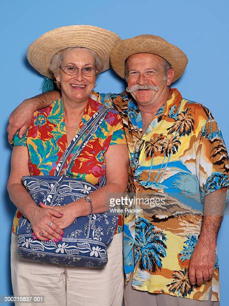 Senior couple wearing Hawaiian shirts, smiling, portrait