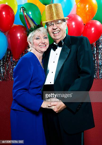 Senior couple wearing party hats celebrating New Years Eve, smiling