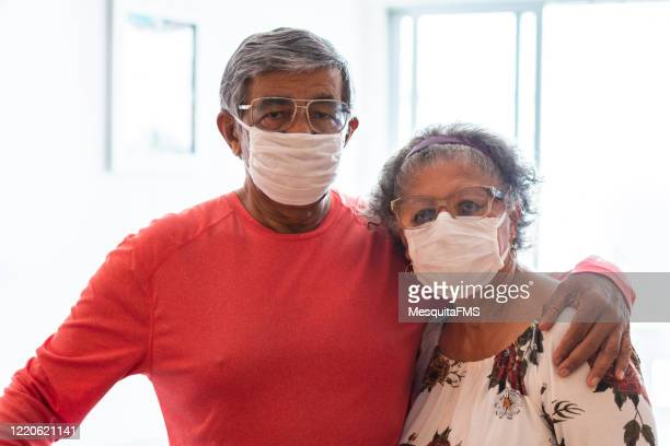 senior couple wearing protective mask - n95 respirator mask stock pictures, royalty-free photos & images
