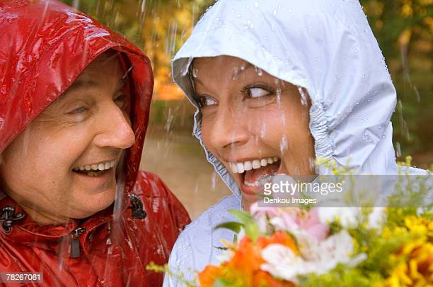 A senior couple wearing raincoats in the rain.