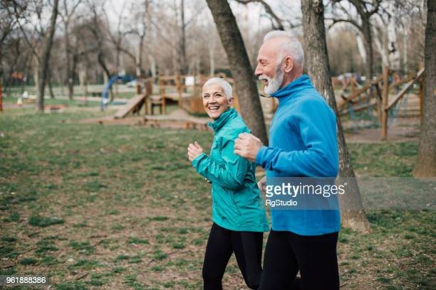 Senior couple wearing sport clothes jogging at the park