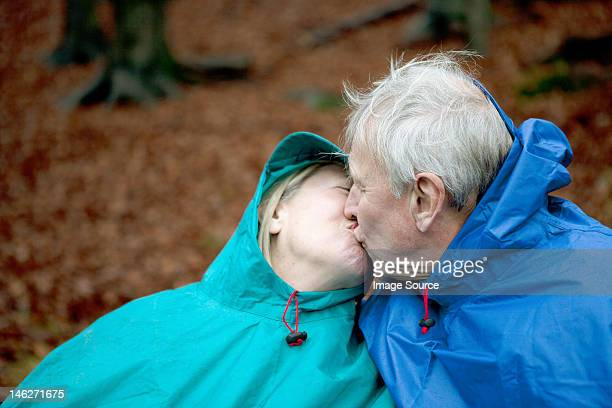 Senior couple wearing waterproofs and kissing