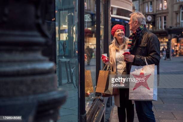 senior couple window shopping in town - shop stock pictures, royalty-free photos & images