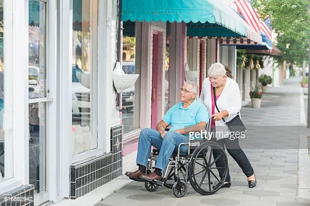 Senior couple window shopping, man in wheelchair