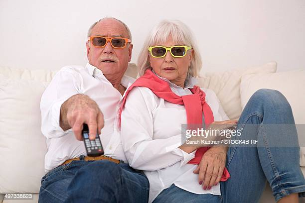 Senior couple with 3d glasses on couch watching TV