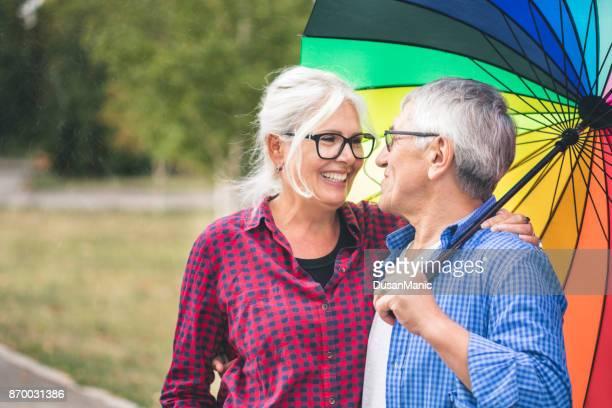 Senior couple with a rainbow umbrella
