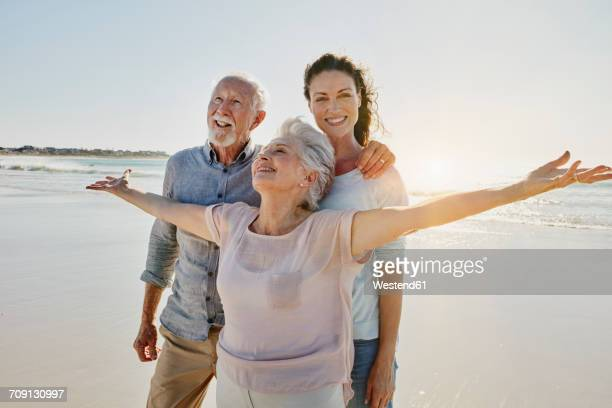Senior couple with adult daughter on the beach