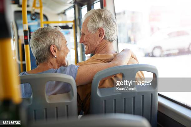 Senior couple with arms around each other, riding with public bus