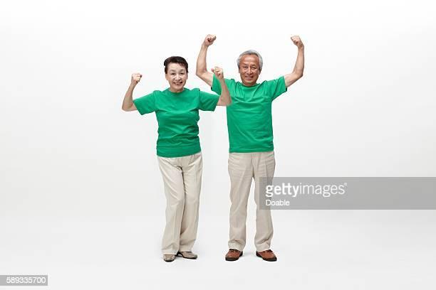 Senior couple with arms raised