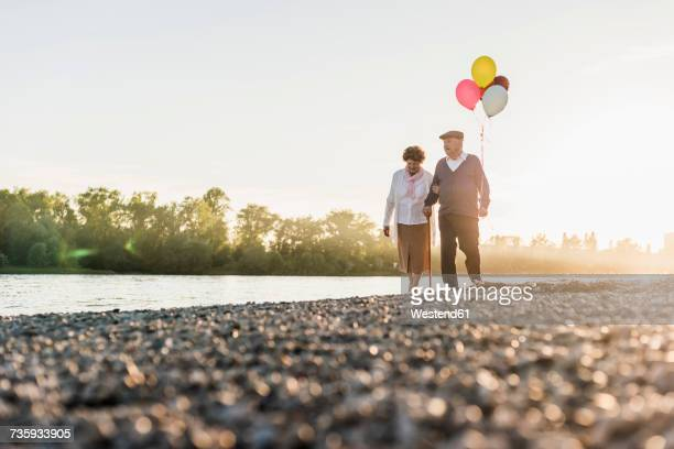 Senior couple with balloons strolling at riverside
