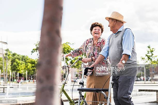 Senior couple with bicycle and wheeled walker