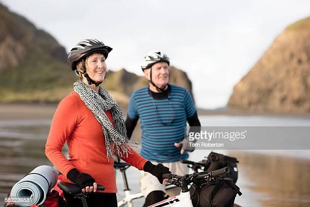 Senior couple with bikes enjoying scenery on beach