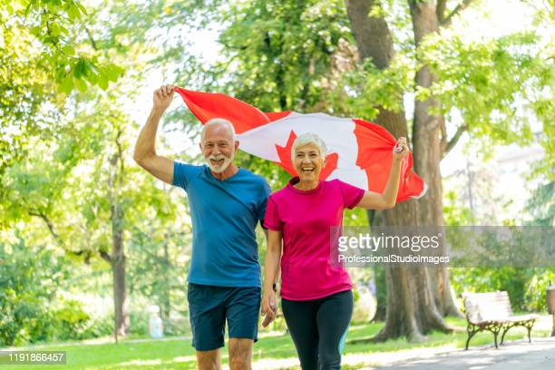 senior couple with canadian flag in public park - canadian flag stock pictures, royalty-free photos & images