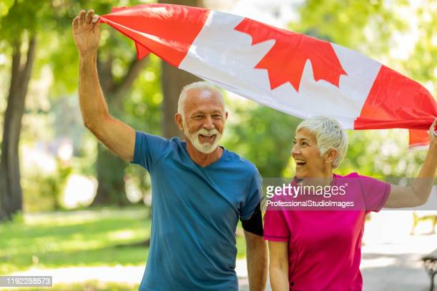 senior couple with canadian flag in public park - canada day stock pictures, royalty-free photos & images