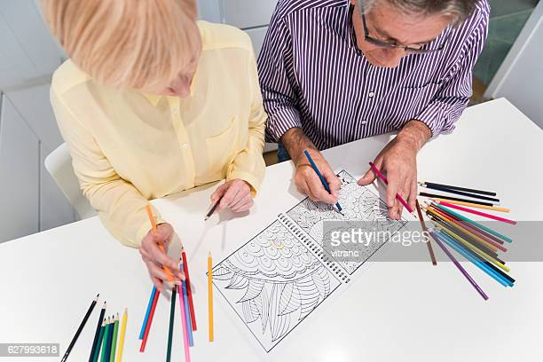 senior couple with coloring book - coloring stock photos and pictures