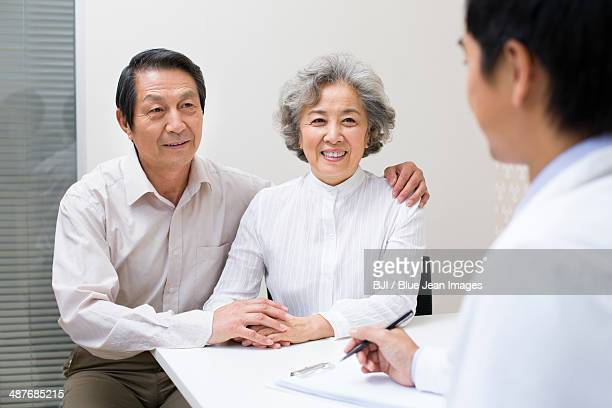 Senior couple with doctor in hospital