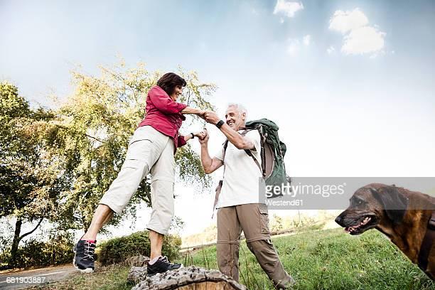 senior couple with dog on a hike - frau 65 jahre stock-fotos und bilder
