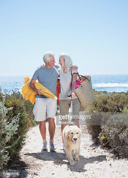 senior couple with dog walking on beach path - woman carrying tote bag stock photos and pictures