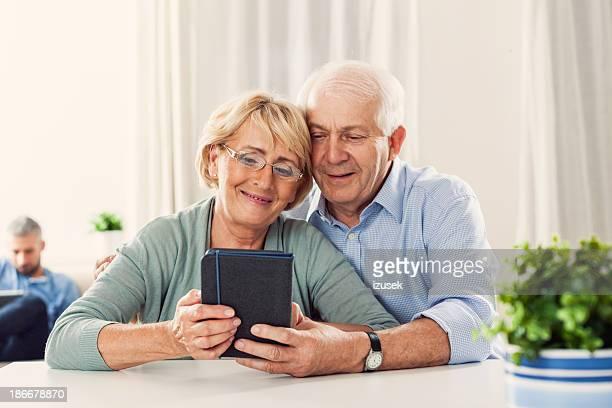 Senior couple with e-reader