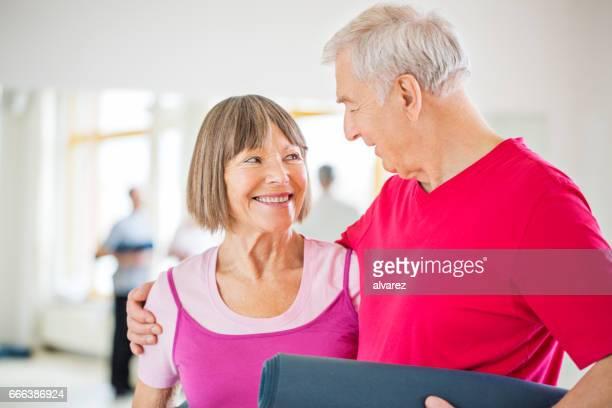 Couple de personnes âgées avec des tapis d'exercice dans la salle de gym