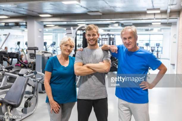 senior couple with fitness coach at rehab gym - izusek imagens e fotografias de stock