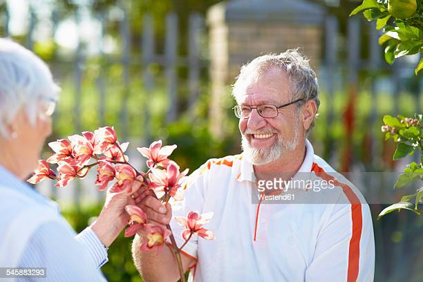 Senior couple with flower blossom in park