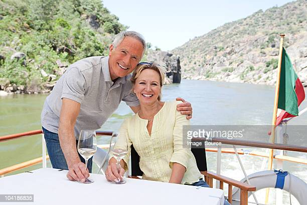 senior couple with glasses of wine on a boat holiday - douro valley stock photos and pictures