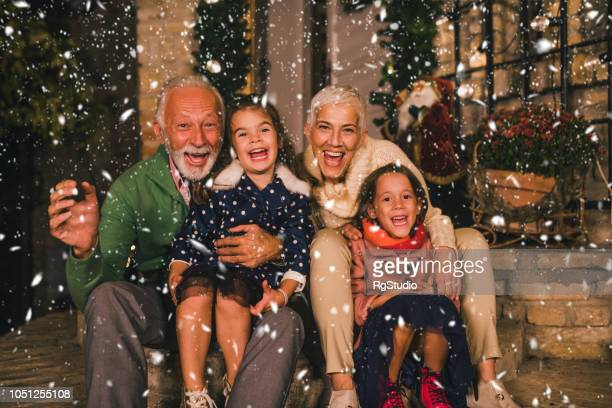 senior couple with granddaughters - christmas photos stock photos and pictures