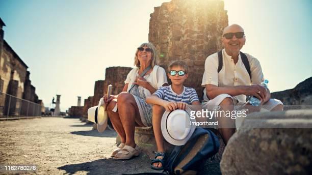 pareja mayor con nieto visitando ruinas antiguas - pompeya fotografías e imágenes de stock