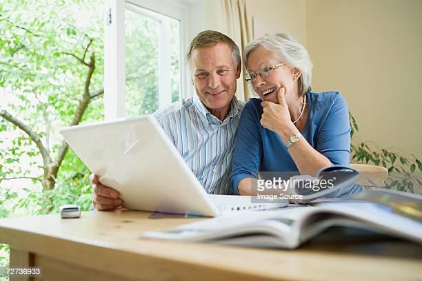 couple âgé avec ordinateur portable et de brochures