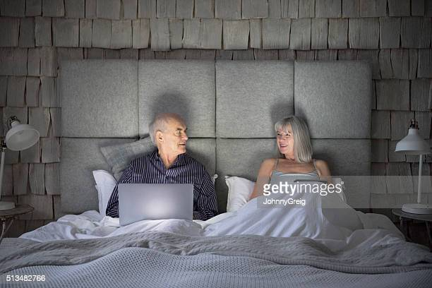 Senior couple with laptop in bed looking at each other
