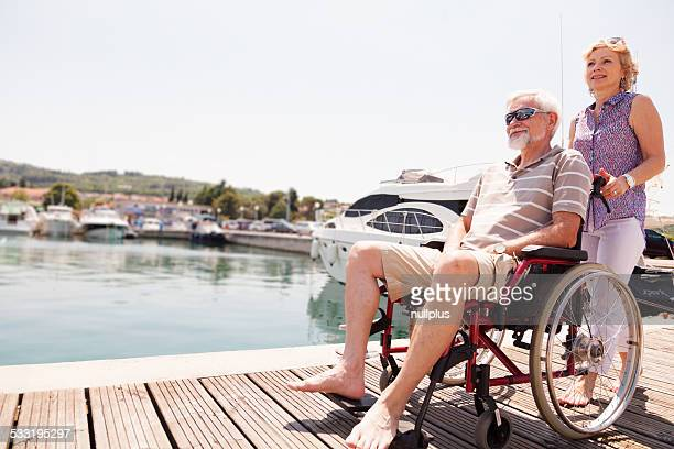 senior couple with man in wheelchair on pier