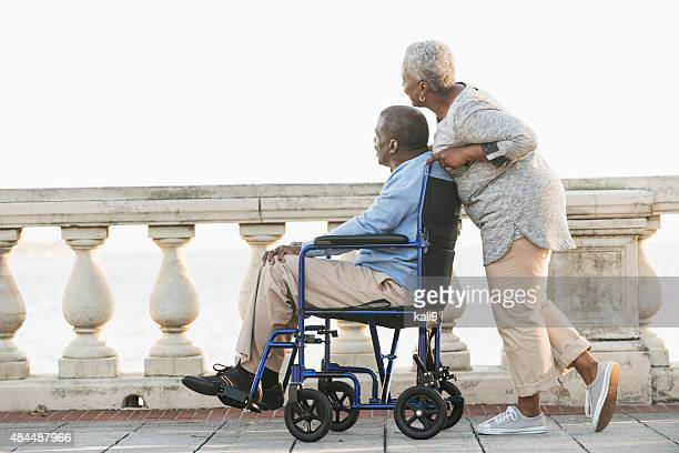 senior couple with man in wheelchair - aaien stockfoto's en -beelden