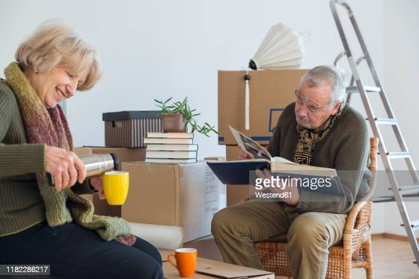 senior couple with photo album and hot drink surrounded by cardboard boxes in an empty room - hot women pics ストックフォトと画像