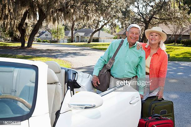 Senior couple with suitcases and convertible