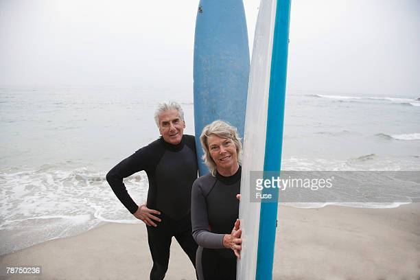 senior couple with surfboards by the ocean - arms akimbo stock pictures, royalty-free photos & images