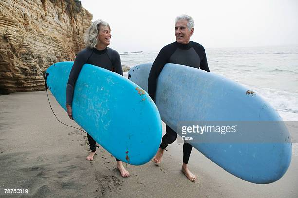 Senior Couple with Surfboards by the Ocean