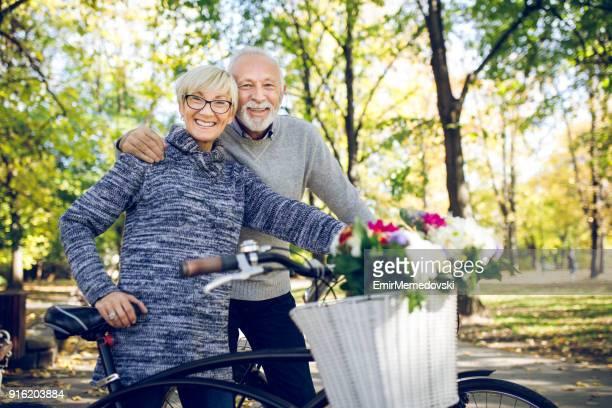 casal sênior com as bicicletas no parque - montar - fotografias e filmes do acervo
